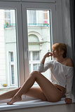 charming girl sitting near window