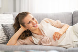 Portrait of happy young woman laying on sofa