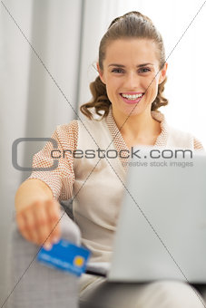 Portrait of happy young housewife with laptop holding credit car