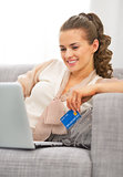 Young housewife with credit card using laptop