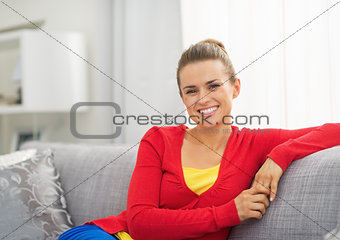 Portrait of happy young woman sitting on sofa