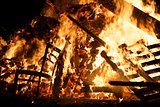 Wooden chair and pallets burning in bonfire