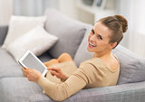Portrait of happy young woman sitting on sofa and using tablet p