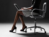 Businesswoman using laptop (low section)