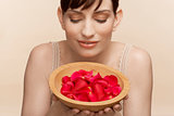 Mid adult woman holding bowl of petals