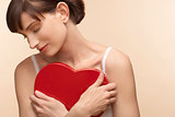 Mid adult woman holding heart shaped chocolate box