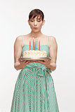 Mid adult woman blowing candles on birthday cake