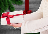 Composite image of woman offering a gift box