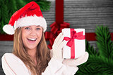 Composite image of festive blonde holding a gift