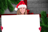 Composite image of festive blonde holding a poster