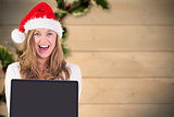 Composite image of festive blonde showing a laptop