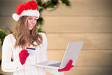 Composite image of festive blonde shopping online with laptop