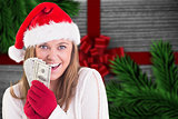 Composite image of festive blonde showing fan of dollars