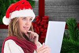 Composite image of festive blonde looking at tablet pc