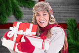 Composite image of happy blonde in winter clothes holding gifts