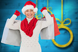 Composite image of festive woman holding shopping bags