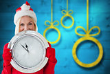 Composite image of happy festive blonde with clock
