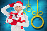Composite image of festive woman holding gifts