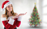 Composite image of sexy santa girl presenting with hands