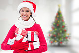 Composite image of festive brunette holding gifts