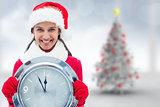 Composite image of festive brunette holding clock