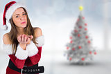 Composite image of sexy santa girl blowing over hands