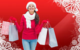 Composite image of festive brunette holding shopping bags