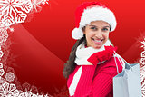 Composite image of festive brunette holding shopping bag