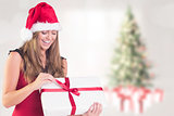 Composite image of festive blonde opening a gift
