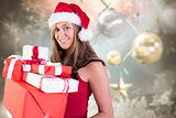 Composite image of festive blonde holding pile of gifts