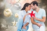 Composite image of young couple holding gift