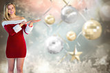 Composite image of pretty girl presenting in santa outfit