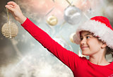 Composite image of festive girl hanging decoration