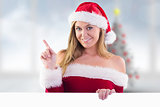 Composite image of festive blonde smiling and pointing