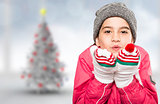 Composite image of wrapped up little girl blowing over hands
