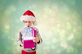 Composite image of festive boy holding a gift