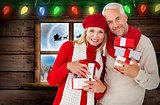 Composite image of happy festive couple with gifts