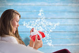 Composite image of pretty blonde relaxing on the couch with gift