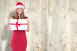 Composite image of festive blonde showing a gift