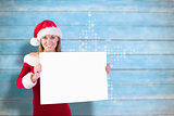 Composite image of festive blonde smiling at camera holding poster