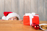 Composite image of festive boy peeking over table