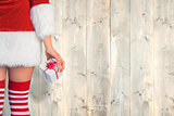 Composite image of pretty girl in santa outfit holding gift