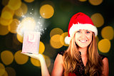 Composite image of festive blonde holding a gift bag
