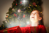 Composite image of little girl opening a magical christmas gift