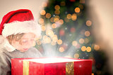 Composite image of child opening his christmas present
