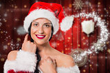 Composite image of smiling woman wearing a santa hat
