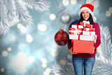 Composite image of woman holding many christmas presents