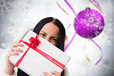 Composite image of woman holding a large present