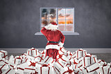 Composite image of santa standing on pile of gifts