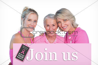 Composite image of embracing women wearing pink tops and ribbons for breast cancer